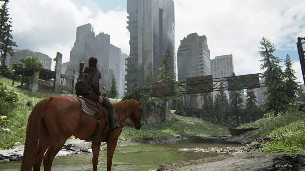 A screenshot from The Last of Us Part II showing Ellie on horseback looking at the ruins of a post-apocalyptic Seattle