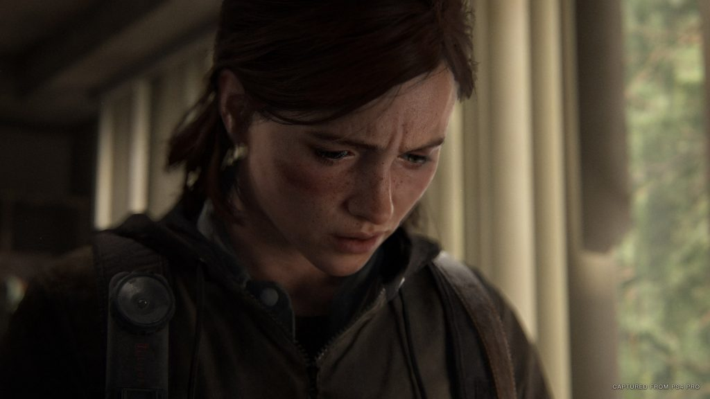 A screenshot from The Last of Us Part II showing a close-up of Ellie's face, while she looks upset.